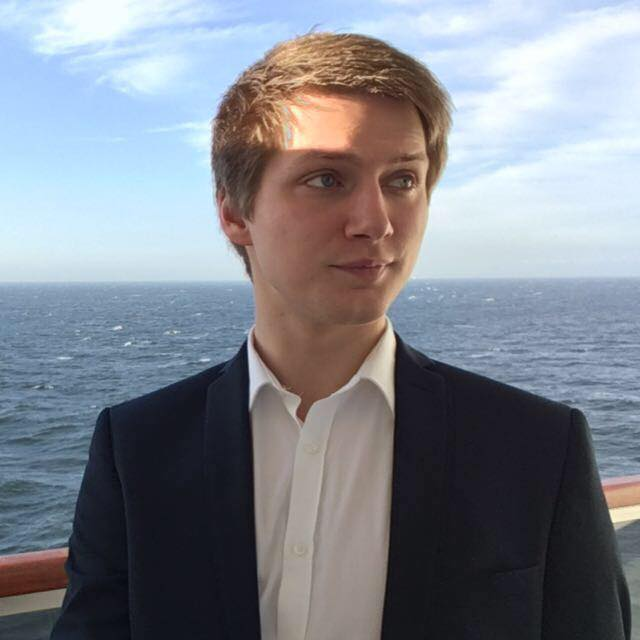 Profile photo of Adam Greenough, he is looking right on a ship, there is the open sea and blue sky in the background