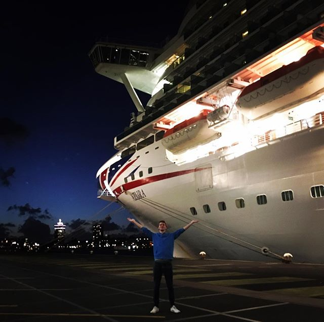 Adam with arms in air at night, large cruise ship and cityscape in background